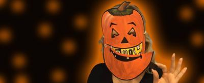 A creepy Halloween pumpkin mask on a black background.