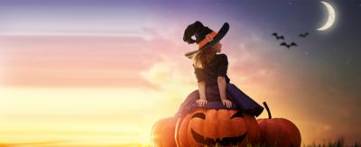 A girl dressed as a witch sitting on a giant pumpkin looking at the moon.