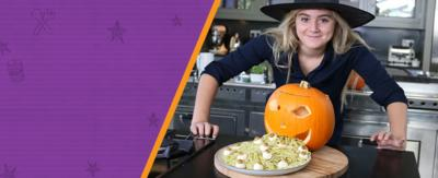 A young girl with blonde hair and wearing a witches hat, leans over a kitchen counter with a cut out pumpkin sat on a board behind a plate full of pesto spaghetti with olives and mozzerella that looks like the pumpkin is vomiting the spaghetti. (Matilda Ramsay).