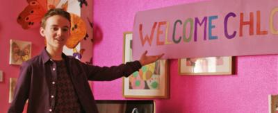 Ryan pointing to a welcome Chloe sign.