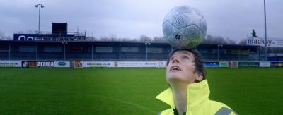 A man in a high-viability jacket doing football freestyle.