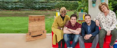Four people sit in a group smiling at the camera (Bake Off Judges and Sam and Mark).