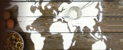 A map of the world drawn in flour spread across a tabletop.