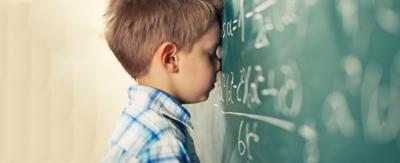 Little boy with his forehead against a green chalkboard covered in algebra.