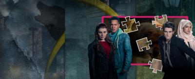 Two girls and two boys stand in pairs either side of the picture, with a zoomed in picutre of an unfinished jigsaw of a wolf behind them. (Wolfblood characters, Jana and TJ, and Matai and Selina).