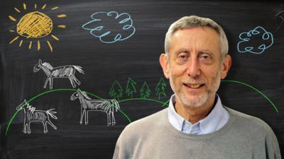 Michael Rosen from Poetry Playtime in front of a blackboard picture of white horses.