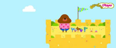 Hey Duggee and the Squirrel club on top of a sandcastle