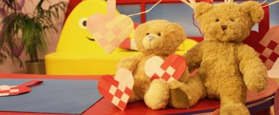 Two teddy bears holding paper hearts.