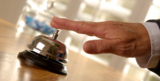 Person's hand ringing reception style bell.  From iStock.