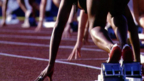 Runners on starting blocks on track