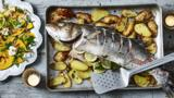 Whole sea bass baked on anchovy and garlic potatoes with a pickled pumpkin and walnut salad