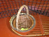 The basket, sunk into the floor, into which the real tennis balls are captured