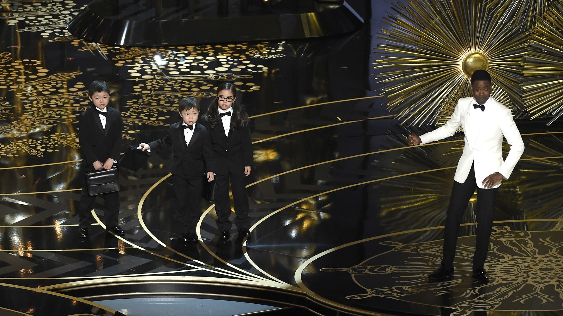 Chris Rock and children, mid-routine, on the 2016 Academy Awards telecast.