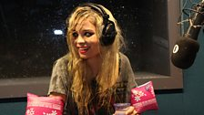 Nina Nesbitt wearing pink arm bands and drenched head to toe
