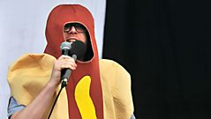 Huw in a hot dog on stage at Reading Festival