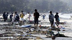 People walk through debris
