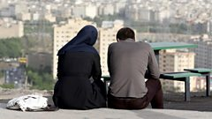 An Iranian couple sit looking out across Tehran