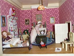 A doll's house room with a sampler on the wall