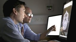 Photo: Professor David Menon and colleague looking at brain scans