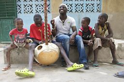 Griot Seckou Keita helping to teach his young cousins to play the Kora at his family home in Senegal