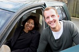 A man and an elderly woman posing by a car
