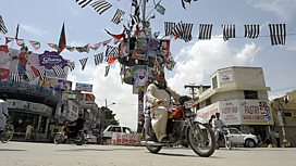 Man passing Pakistan election posters
