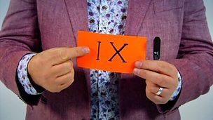 A card with IX on it being held.