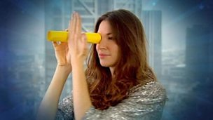 Katherine holding a tube to her eye next to her hand.