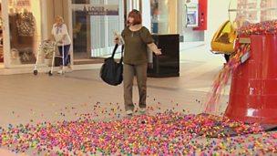 Woman stood beside faulty bubblegum machine.