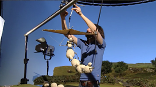 An animator holding up the shaun the sheep characters with rigging.