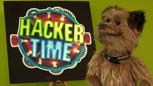 Hacker looks to camera infront of the Hacker Time logo