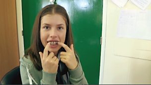 Aimee Kelly, who plays Maddy in Wolfblood, wearing some fangs.