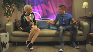 Jessie J and Aidan from Friday Download, sitting on a sofa chatting.