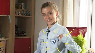 Anouk pointing at her Blue Peter badge