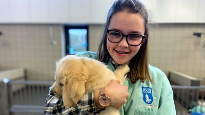 Caitlin holds a guide dog puppy