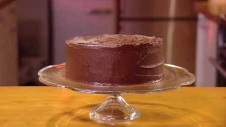 Icing a cake with chocolate ganache