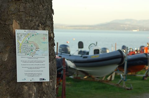 A sign on a tree next to Dalgety Bay sailing club informs the public of radioactive finds