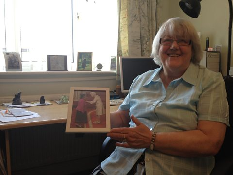 Jean Walker MBE, holding a photo of herself and the Queen