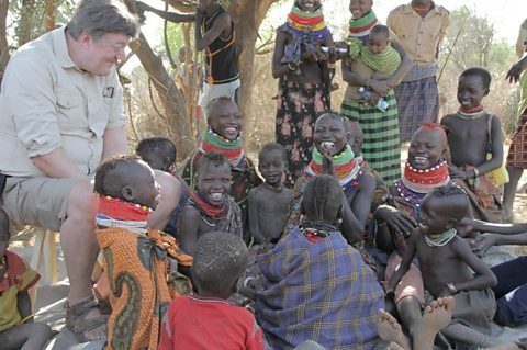 Stephen Fry sitting with the Turkana Tribe