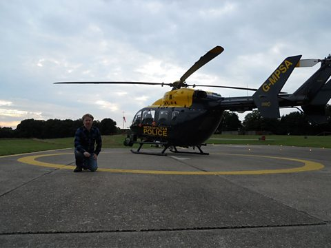 "Paul Farley next to ""India 99"" at the Metropolitan Police Air Support Unit in Epping Forest"