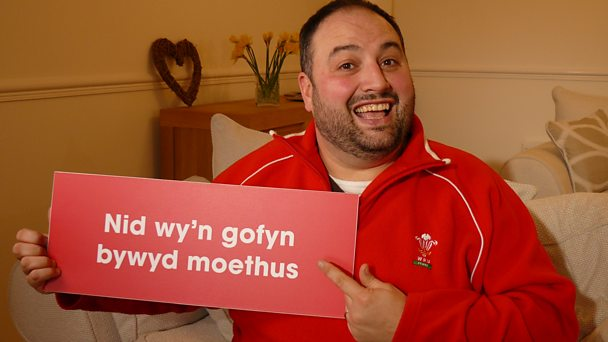 Opera singer Wynne Evans holding a banner displaying the words from Calon Lân.