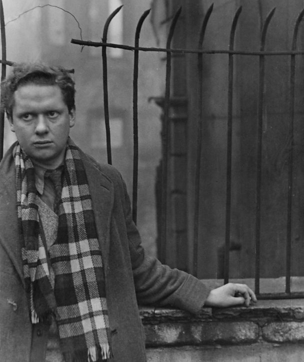 Dylan Thomas standing near bomb-damaged buildings in London, 1945