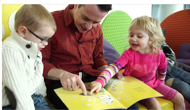 Alex Winters reading story with two children