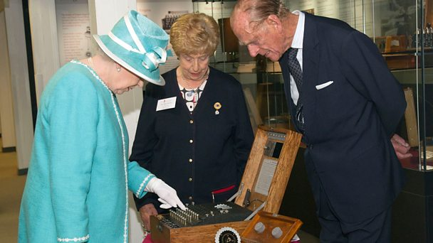The Queen visits Bletchley Park and studies an Enigma machine