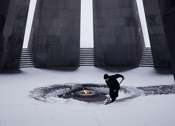 An Armenian woman cleans the Armenian Genocide memorial.