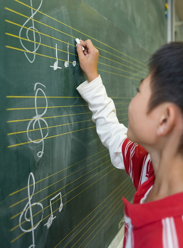 A boy writing musical notation