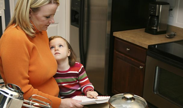 Mother reading recipe to child