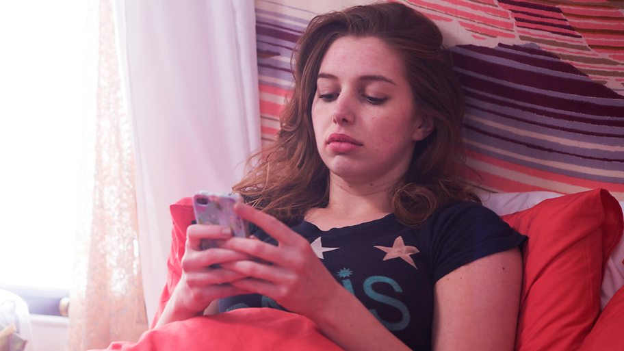 Aisling on her phone in bed
