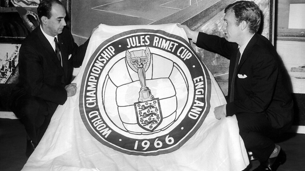 The England captain presents a World Cup flag to a Brazilian Sports Federation delegate.