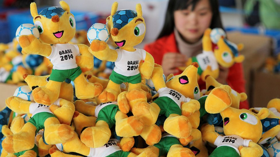 A worker in a factory in Ganyu, China, alongside a mound of 2014 World Cup mascots.